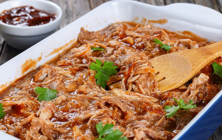 Photo pour delicious Shredded meat tossed in barbecue sauce in dish with wooden fork spatula, on old wooden table with sauce on background, close-up, macro, selective focus - image libre de droit