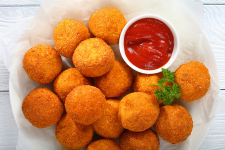 Foto de potato croquettes - mashed potatoes balls breaded and deep fried, served with tomato sauce on plate, view from above, close-up - Imagen libre de derechos