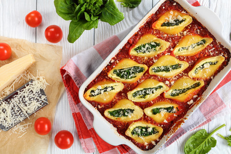Photo for delicious big pasta baked shells stuffed with creamy soft cheese and spinach sprinkled with parmesan cheese in baking dish. grated parmesan cheese on paper, italian recipe, view from above, close-up - Royalty Free Image