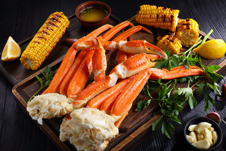 Foto de snow Crab legs served with melted butter, garlic cloves, lemon slices, grilled corn in cobs and fresh parsley on wooden cutting boards, horizontal view from above, close-up - Imagen libre de derechos