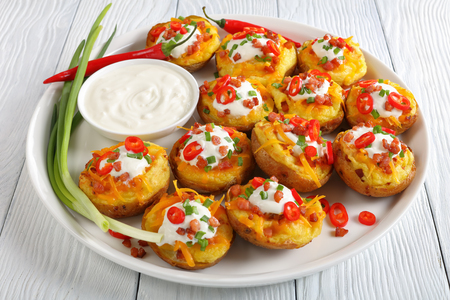 Foto de delicious baked potato halves loaded with grated cheddar cheese, bacon, chili peppers slices, sour cream on white platter with sour cream in bowl, view from above, close-up - Imagen libre de derechos