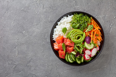 Photo pour Raw Organic Ahi salmon Poke Bowl with rice, seaweed, avocado rose, radish, carrot, cucumber and green salad, sprinkled with spring onion and sesame seeds, view from above, flatlay - image libre de droit