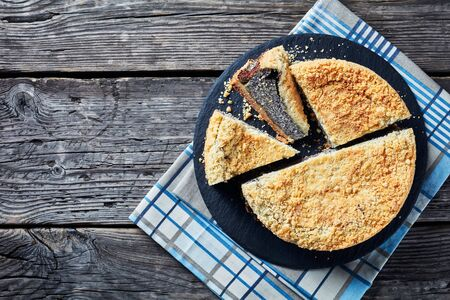 Photo for overhead view of delicious Poppy Seed Crumble Cheesecake sliced on a black slate round plate on a rustic wooden table, horizontal view from above, close-up - Royalty Free Image