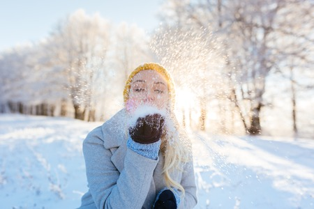Photo for Winter girl blowing snow in frosty winter park, young woman having fun in winter park. Sunset shot with selective focus - Royalty Free Image