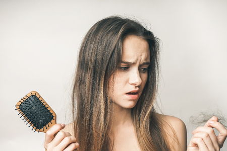 Foto de the girl with a comb in hands with the stunned expression is upset because of a torn scrap of hair - Imagen libre de derechos