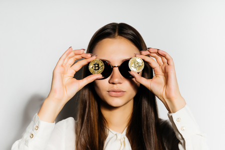 Photo pour steep, serious girl with black glasses put a coin to her eyes. Money, electronic money, crypto currency, bitcoins, isolated - image libre de droit