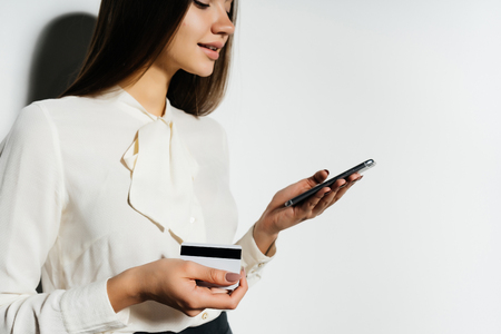Photo pour young business woman looking into her smartphone and holding a bank card - image libre de droit