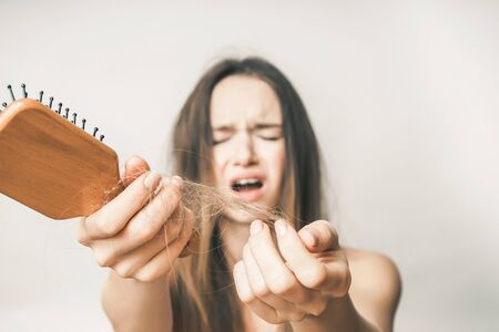 Photo pour Lost hairs on comb close up,she is very sad, on a white background - image libre de droit