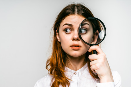 Foto de red-haired girl looking in magnifier to the side, isolated on white background - Imagen libre de derechos