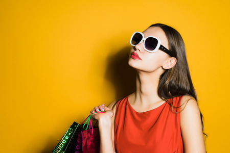 Photo pour beautiful young girl in sunglasses loves shopping, bought a lot of things, in a black penny - image libre de droit