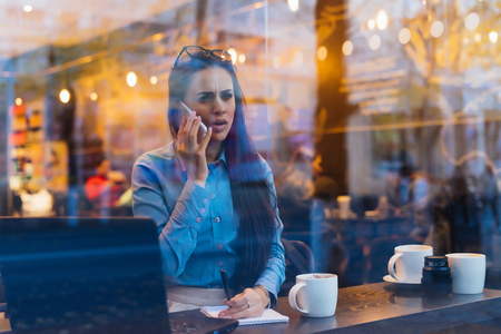 Photo for dissatisfied busy girl freelancer is negotiating by phone, in a cafe - Royalty Free Image