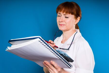Photo for woman on a blue background in a medical dressing gown examines documents - Royalty Free Image