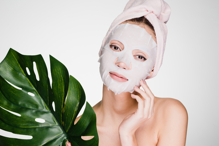 Photo pour cute beautiful girl with a towel on her head, on her face a tissue mask, holds a green leaf, a spa procedure - image libre de droit