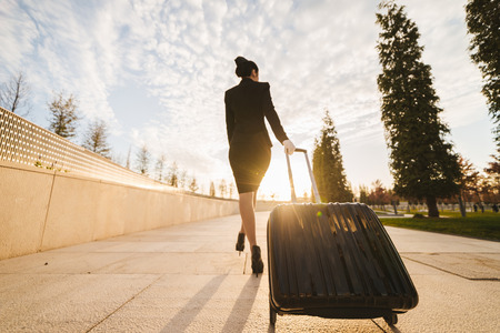Foto de confident slender woman stewardess in uniform goes on a flight with a suitcase in the rays of the sun - Imagen libre de derechos