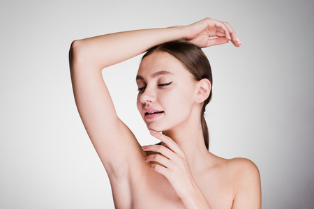Photo pour a surprised woman on a gray background shows her armpits - image libre de droit