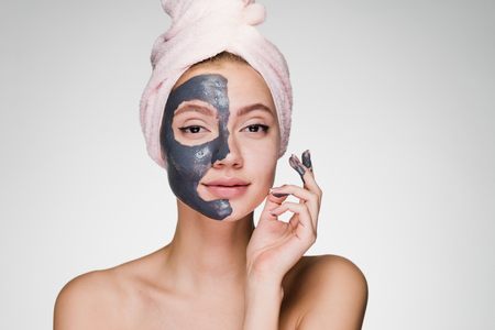 Photo for a young attractive girl with a pink towel on her head applied a useful clay mask to half the face - Royalty Free Image