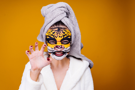 Photo pour a woman stands on a yellow background in a tiger mask - image libre de droit