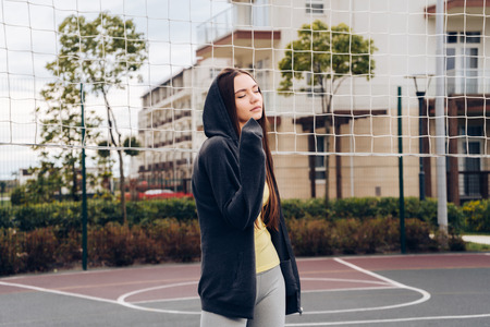 Photo pour a cute young girl rests after a difficult workout at an outdoor sports field, leads a healthy lifestyle - image libre de droit