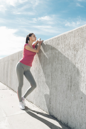 Photo pour high slender girl with a beautiful figure resting after a difficult workout under the blue sky - image libre de droit