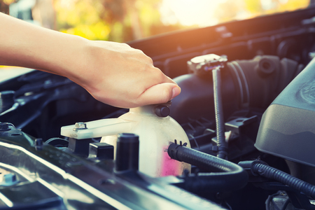 Foto per Asian girl's hand checking level of coolant car engine. - Immagine Royalty Free