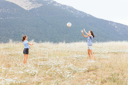Foto de Two sisters passing a ball in the meadow with the mountains in the background in a beautiful place - Imagen libre de derechos