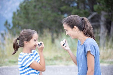 Foto de Two happy sisters very close talking and joking with a walkie-talkie - Imagen libre de derechos