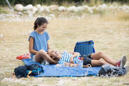 Foto de Two sisters talking and laughing on the mountain and the youngest one is lying on the older girl's legs - Imagen libre de derechos