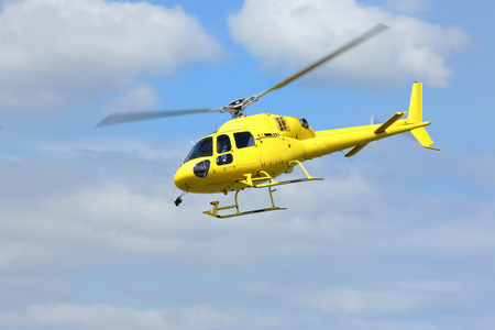 Foto de Helicopter rescue, Yellow helicopter in the air while flying on blue sky.  - Imagen libre de derechos