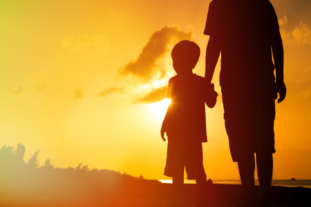 Foto de silhouette of father and son holding hands at sunset sea - Imagen libre de derechos