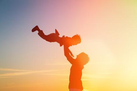 Photo pour father and little son silhouettes play at sunset sky - image libre de droit