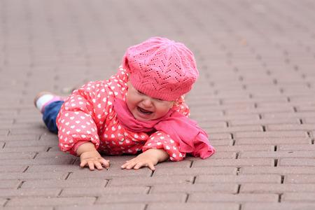Foto de crying little girl fall off on sidewalk, kids safety - Imagen libre de derechos