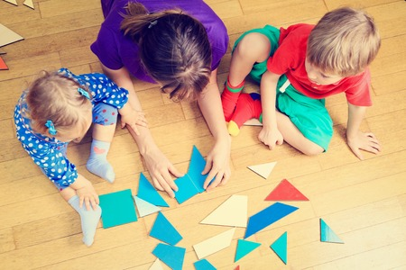 Foto de teacher and kids playing with geometric shapes, early learning - Imagen libre de derechos
