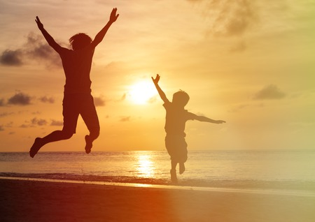 Photo pour father and son jumping at sunset beach, happy family - image libre de droit