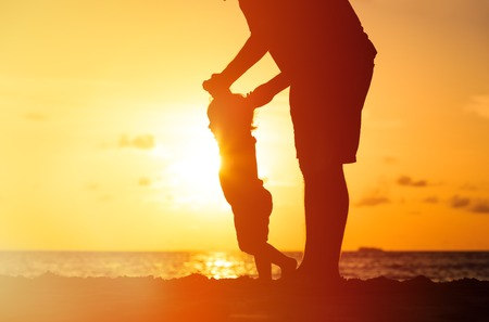 Photo for silhouettes of father and little daughter walking on beach at sunset - Royalty Free Image