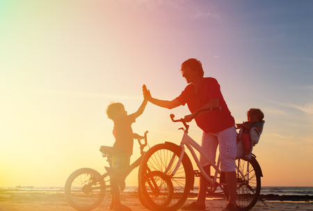 Photo pour Biker family silhouette, father with two kids on bikes - image libre de droit