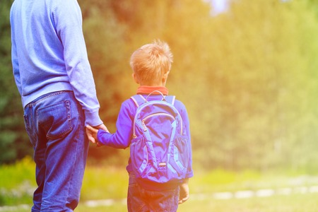 Foto de father holding hand of little son with backpack outdoors, back to school - Imagen libre de derechos