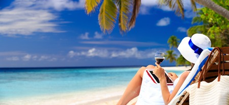 Photo pour panoramic photo of woman drinking wine and looking at touch pad on tropical beach - image libre de droit