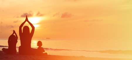 Foto de silhouette of mother and kids doing yoga at sunset, panorama - Imagen libre de derechos