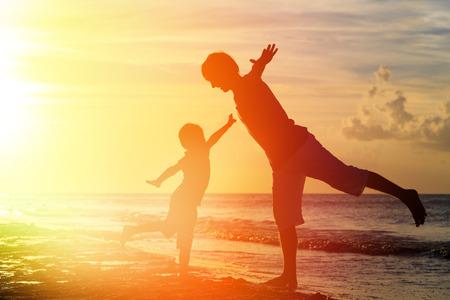 Photo pour father and son having fun on sunset beach - image libre de droit
