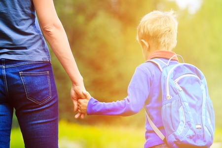 Photo pour Mother holding hand of little son with backpack outdoors, back to school - image libre de droit