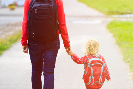 Foto de Mother holding hand of little daughter with backpack going to school or daycare - Imagen libre de derechos