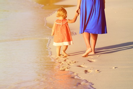Foto de mother and little daughter walking on beach leaving footprint in the sand, family beach travel - Imagen libre de derechos