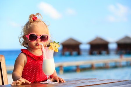 Photo pour cute little girl drinking cocktail on tropical beach resort - image libre de droit