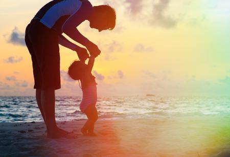 Foto de Silhouette of father and little daughter walking on sunset beach - Imagen libre de derechos