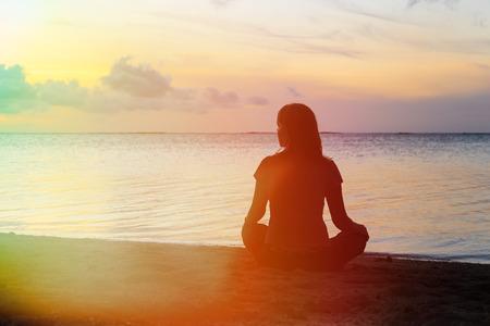 Photo pour young woman meditation on sunset tropical beach - image libre de droit