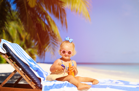 Photo pour cute little girl with sunblock cream on tropical beach - image libre de droit