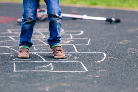 Foto de kid playing hopscotch on playground outdoors, children outdoor activities - Imagen libre de derechos