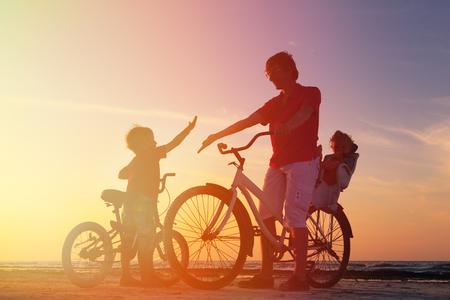 Foto de silhouette of father with two kids on bikes at sunset - Imagen libre de derechos