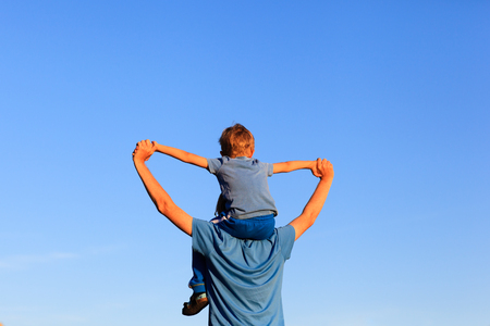 Photo for happy father and little son on shoulders play on sky - Royalty Free Image