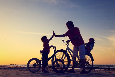 Foto de Biker family silhouette, father with two kids on bikes at sunset - Imagen libre de derechos